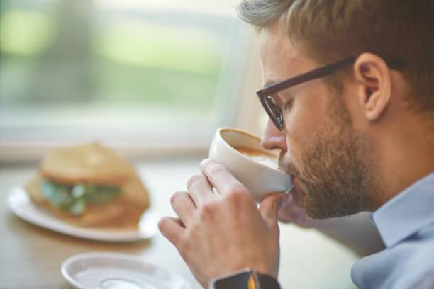 El hombre bebe su café en el trabajo